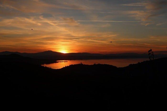 """alt=""""Tramonto del lago Trasimeno visto dal Cantico della Natura"""""""