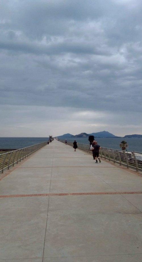 """alt=""""Passeggiando sul pontile di Bagnoli, in lontananza Capo Miseno e le isole di Procida ed Ischia"""""""